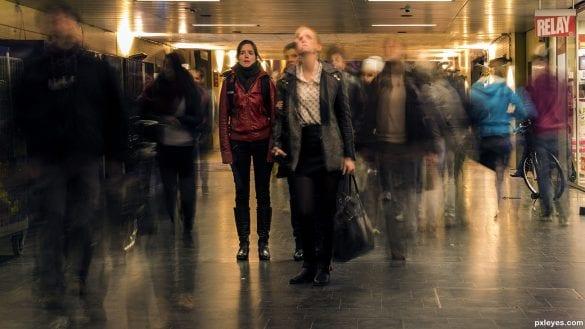 Kalabalıkta hareket eden insanlar. Uzun pozlama yapıldığı için, pozlama boyunca insanların hareketi de görüntüye yansıyor.