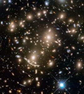 Figür 1: Abell 370 gökada kümesi ve çekimsel merceklenme etkisi. Fotoğraf: HST